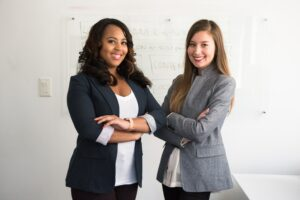 Two young women wearing business attire and smiling